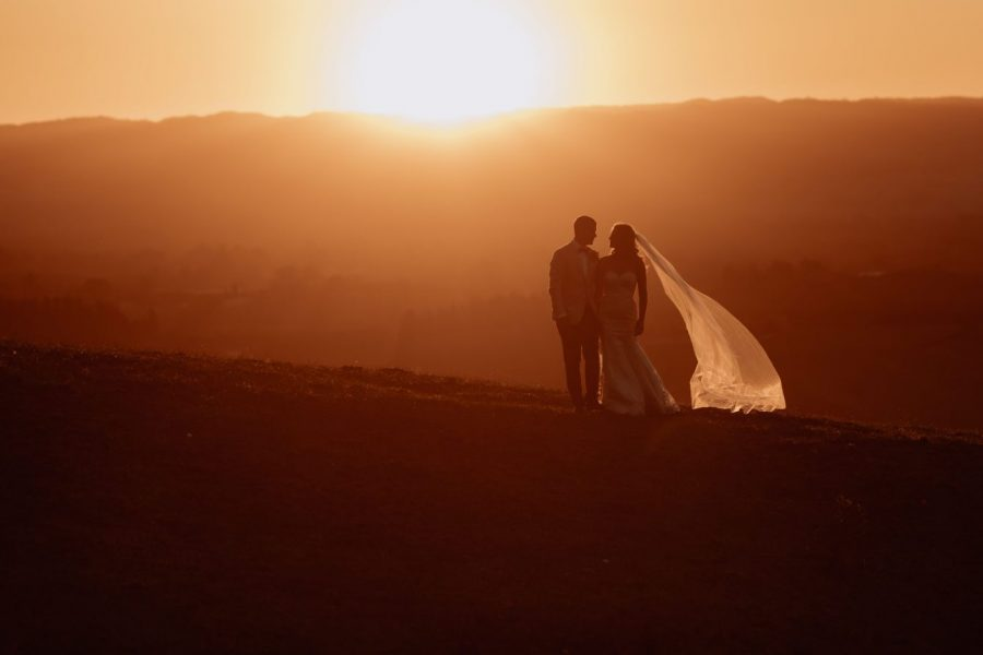 Golden hour sunset photo with bride and groom walking on the hills