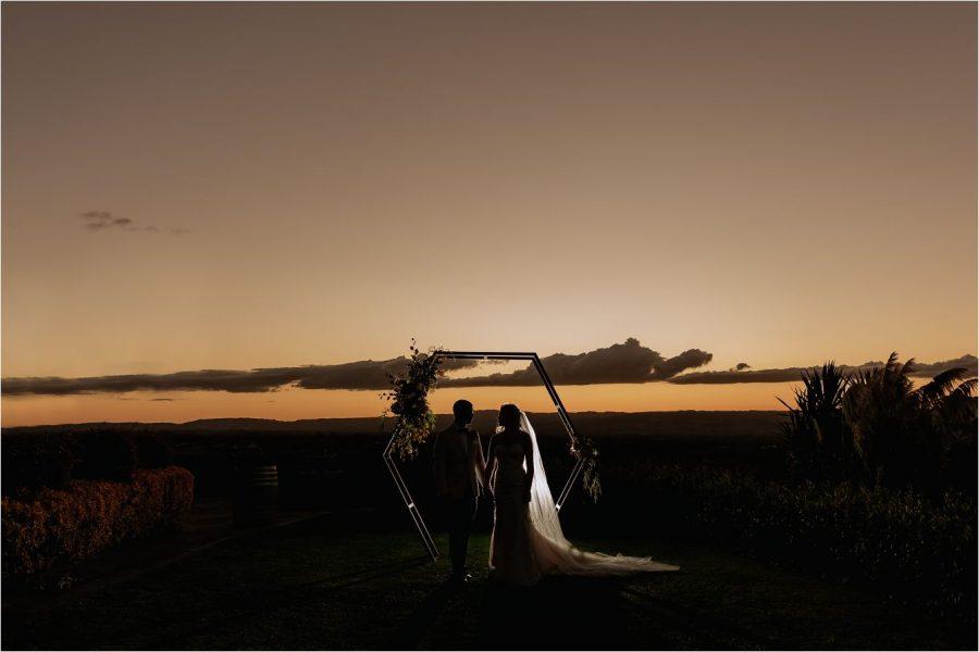 Sunset photo under wedding arch