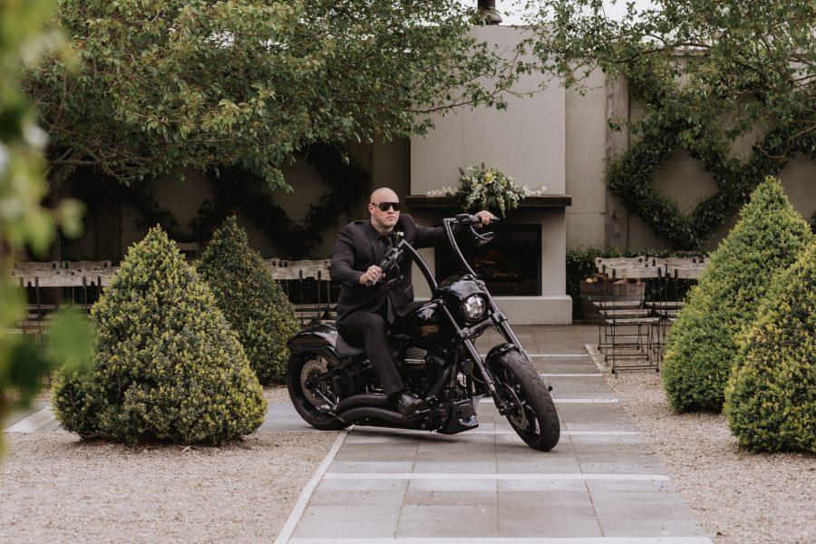 Groom riding Harley Davidson at Tauranga Wedding