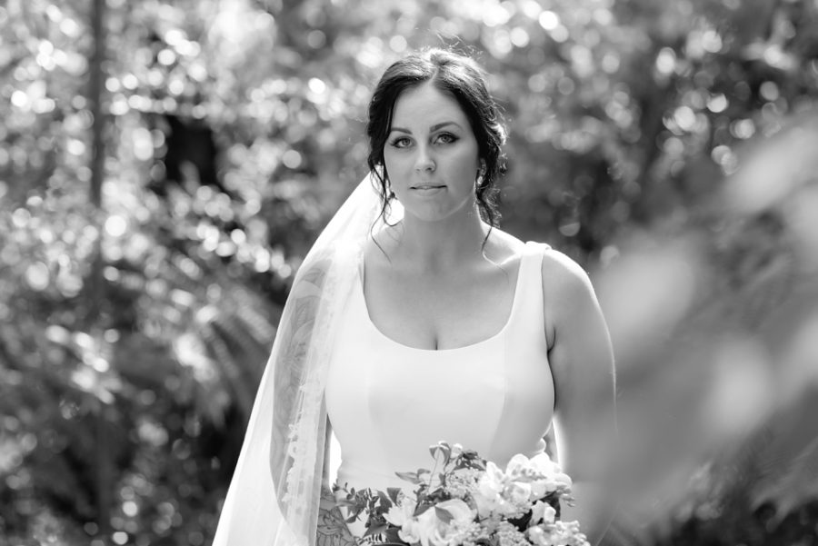 Black and white wedding image of bride in farm track