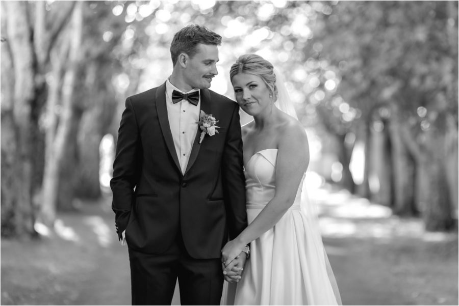 Groom looks at Bride in Black and white on driveway