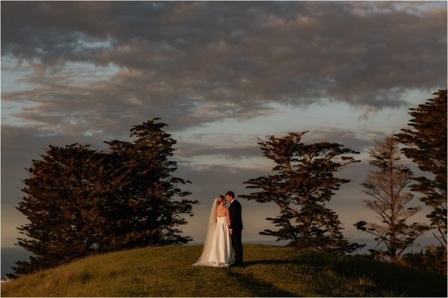 Wedding photo of bride and groom in the country on path leading to trees