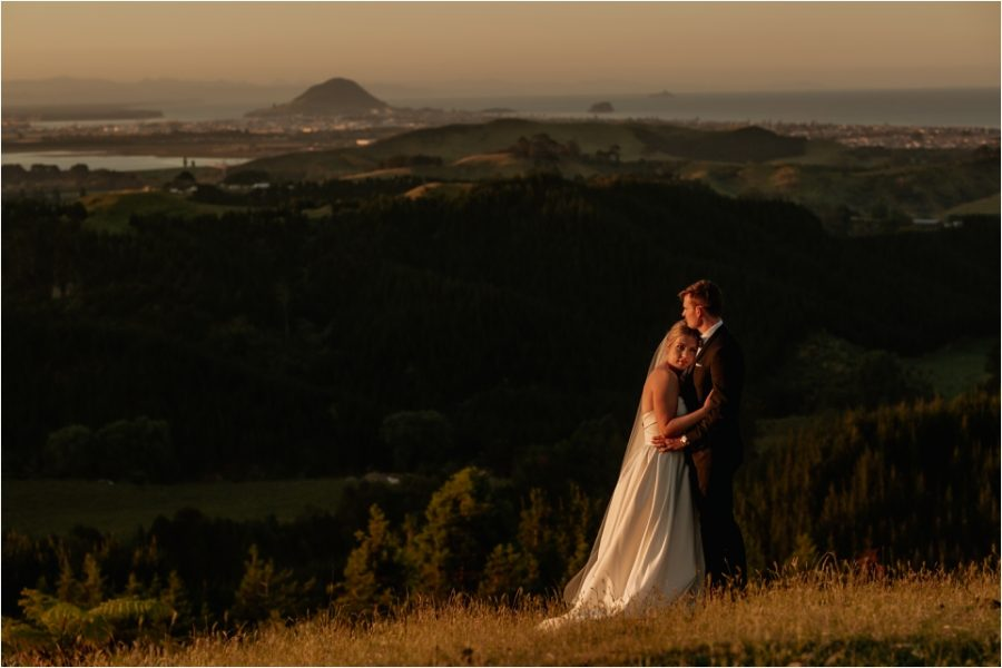 Beautiful sunset photo of bride and groom on hills in New Zealand with Mount Maunganui behind them