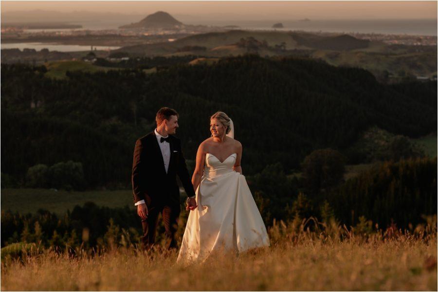 Wedding Photos walking the hills above Tauranga with Mount Maunganui scene