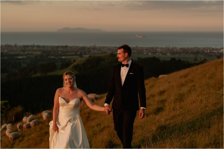 Natural happy wedding photos of couple walking towards camera over the hills of Welcome Bay
