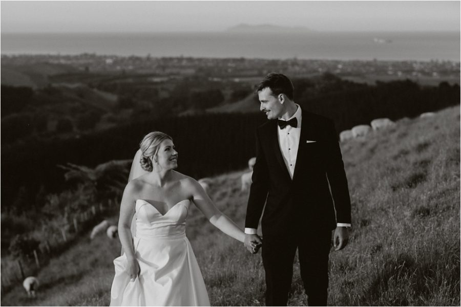Walking happy photos of Bride and Groom with sheep behind them in New Zealand elopement