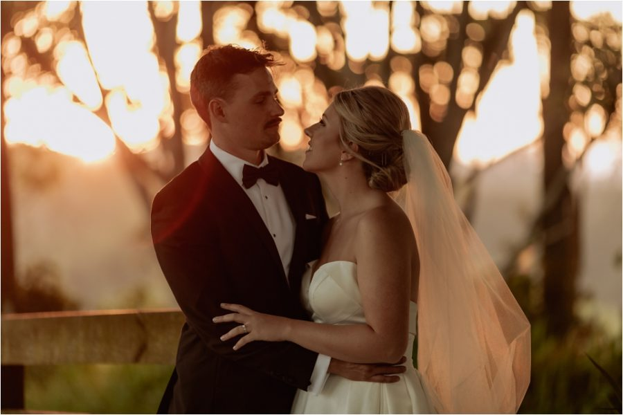 Golden hour photos of elopement with sun behind trees causing bokeh