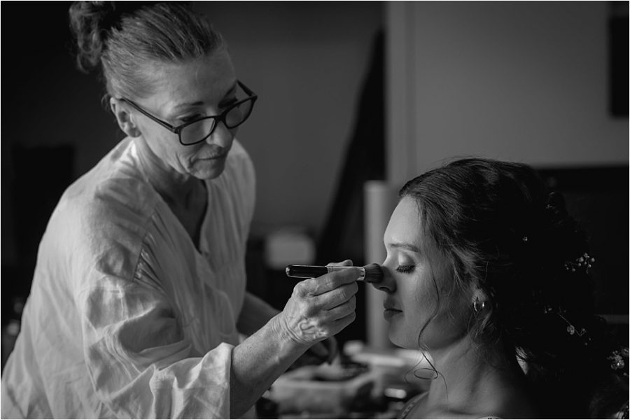 Wedding hair and makeup artist working on bride