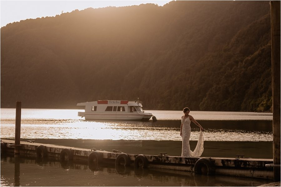 Bride on pier at golden hour with sun setting behind the hills