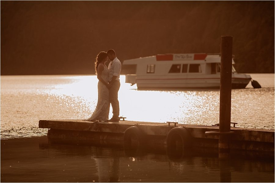 wedding photos on the pier at Lake Okataina with that 70's boat behind them