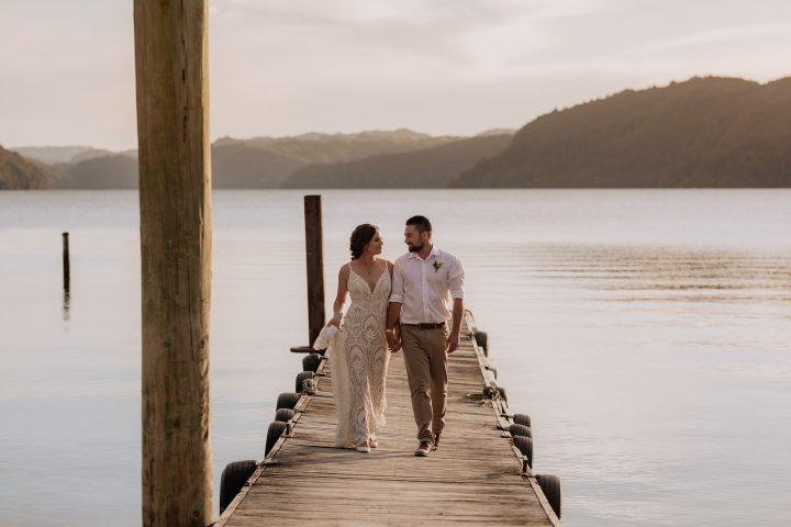 Bridal couple walking on pier at Lake Okataina golden skies