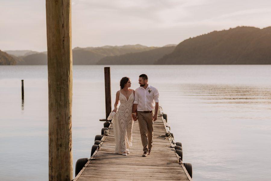 Bridal couple walking on pier at Lake Okataina golden skies