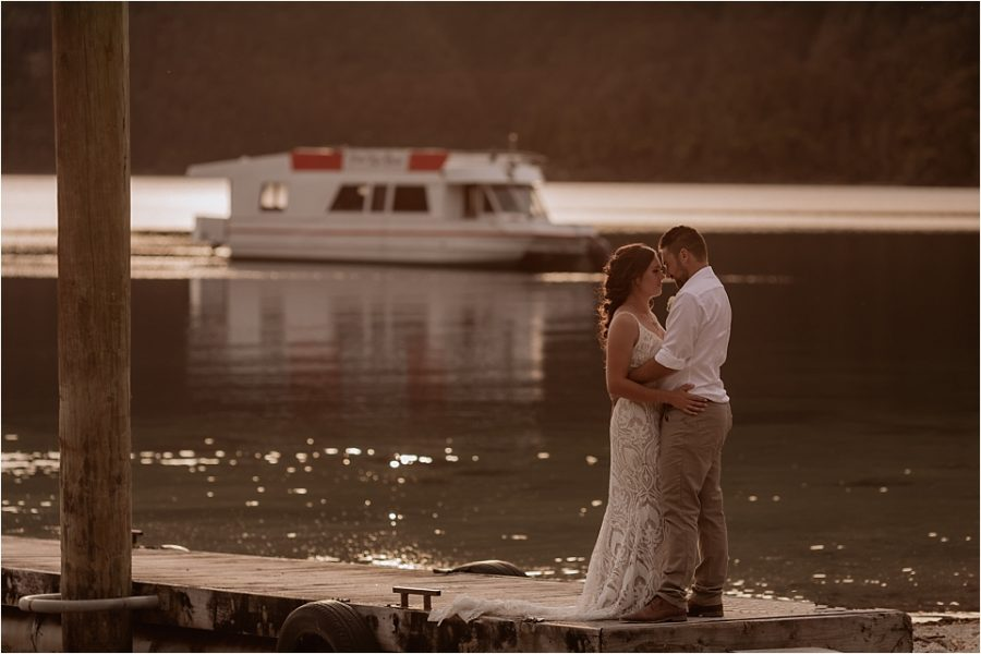 Wedding couple at Lake Okataina pier with 70's boat in the water