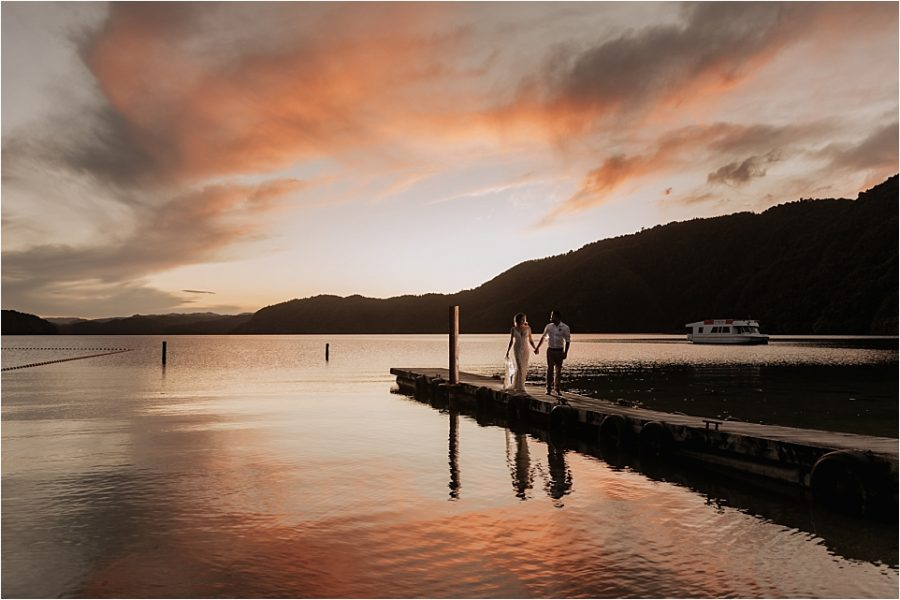 Sunset photo of bride and groom walking on pier at Lake Okataina