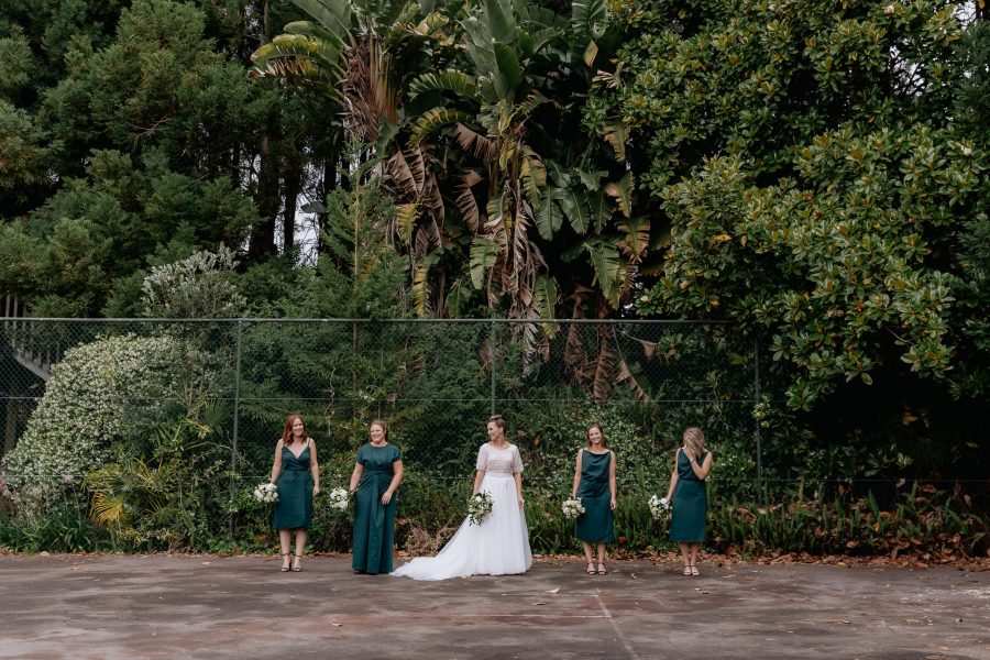 Bride with bridesmaids on tennis court