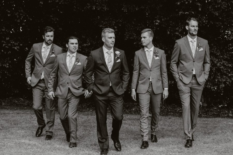 Groom with groomsmen walking black and white photo