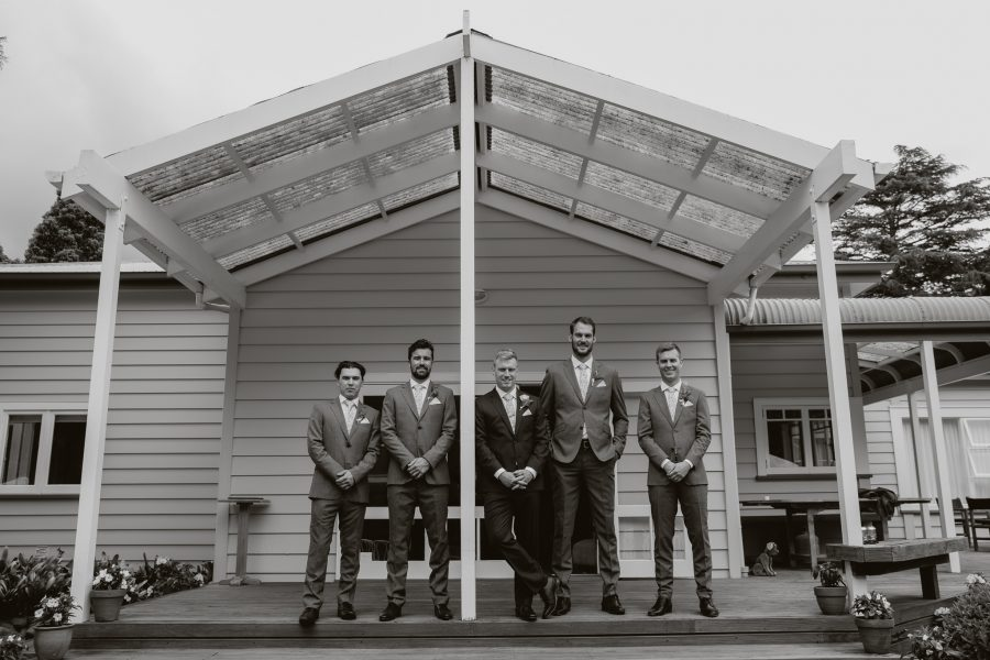 Groom with groomsmen in front of house