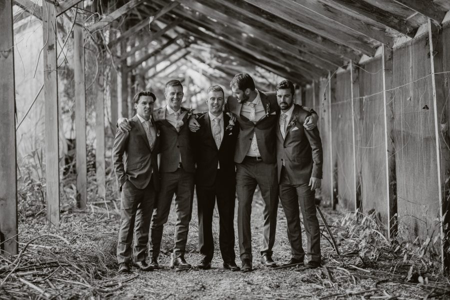 Black and white photo of groomsmen hugging in abandoned building