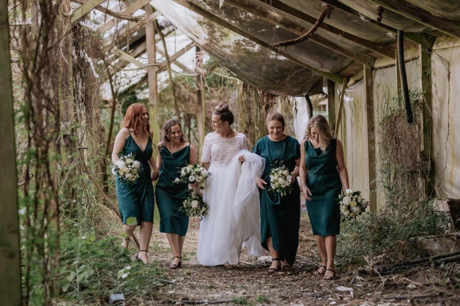 Bride with bridesmaids in abandoned glass house