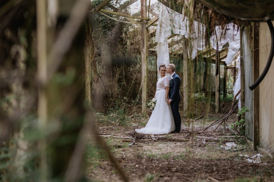 Bride and groom in old abandoned glass house