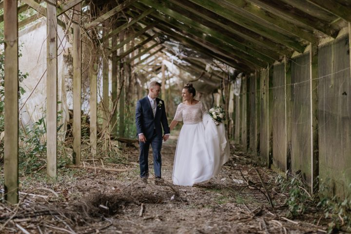 Happy wedding couple walking in rustic abandoned glass house