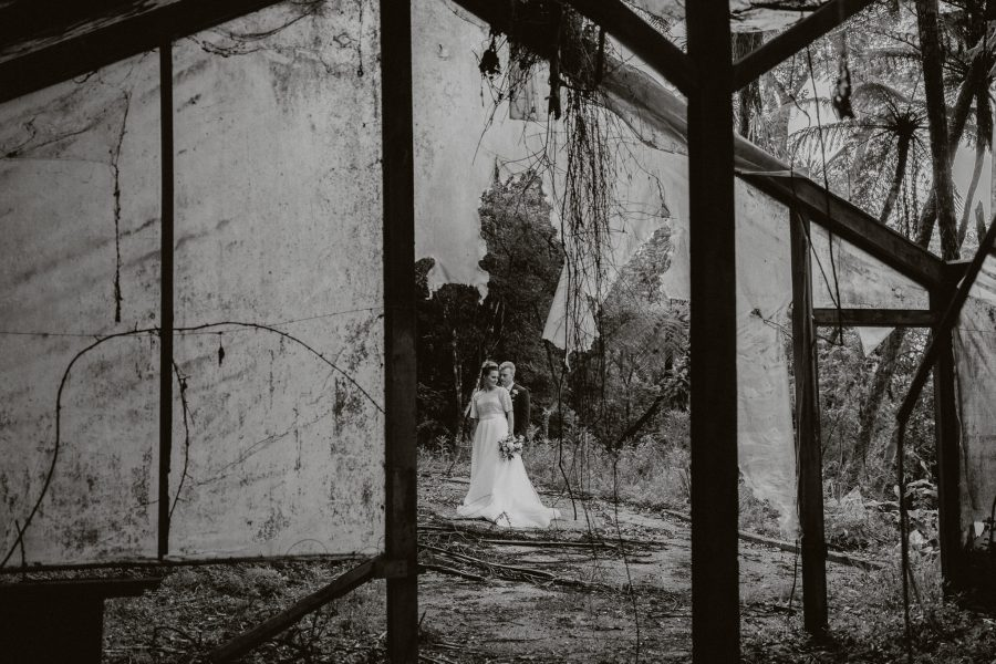 Moody image of bride and groom in abandoned rustic glass house