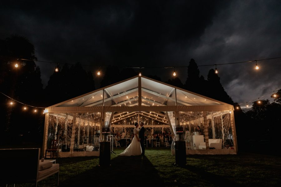 Evening photos of wedding couple in front of marquee at back yard wedding at night time