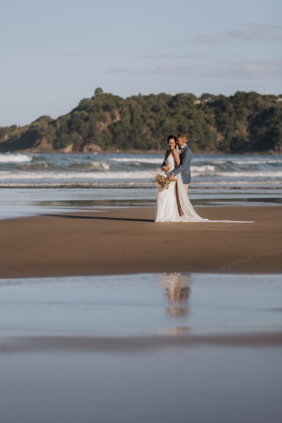 Bride and groom on beach at Hot water beach Coromandel
