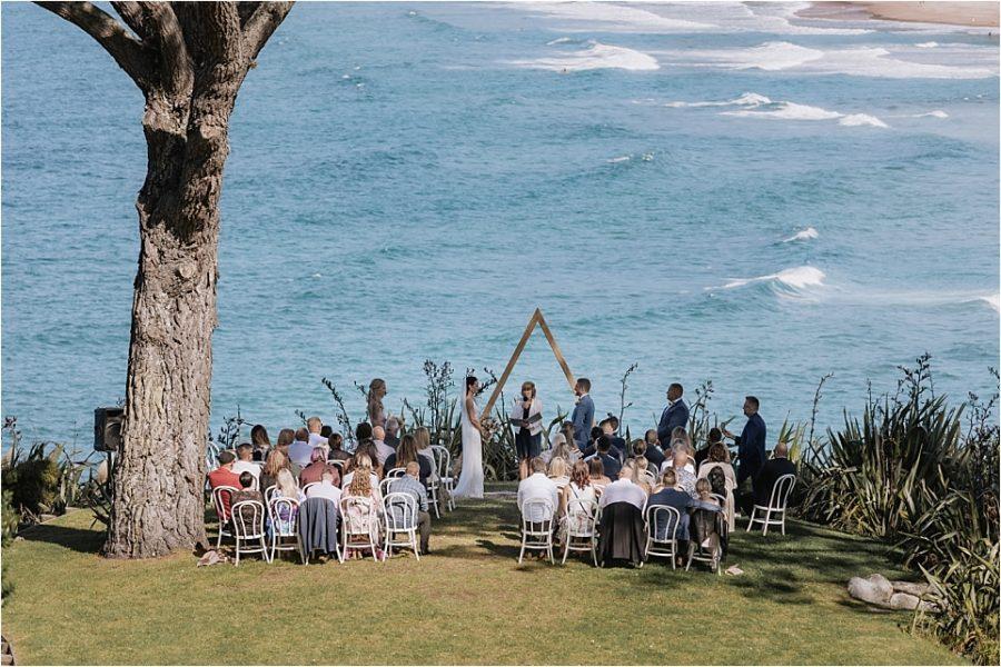 Scene of wedding ceremony in progress overlooking ocean at Orua Beach house