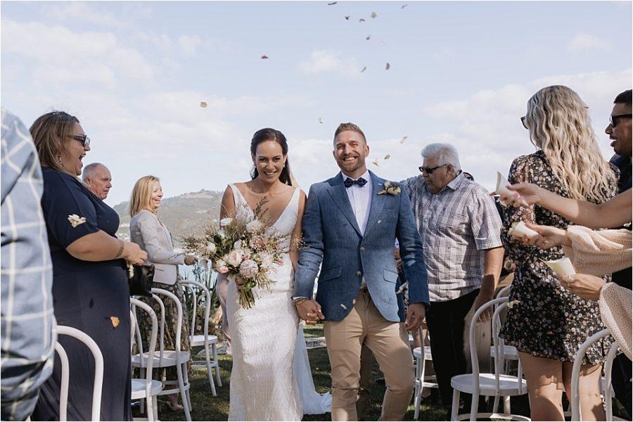Happy aisle walk at Orua Beach house wedding
