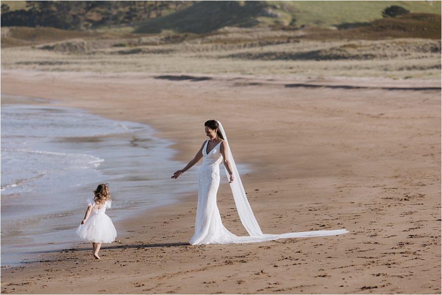 Bride embracing flower girl on Hot Water beach