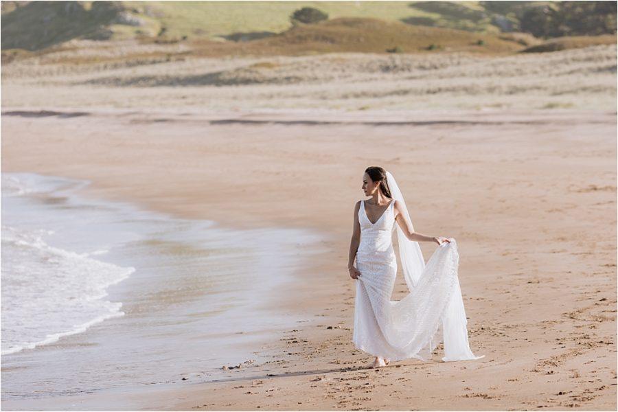 Bride walking beach in Felicity bridal gown