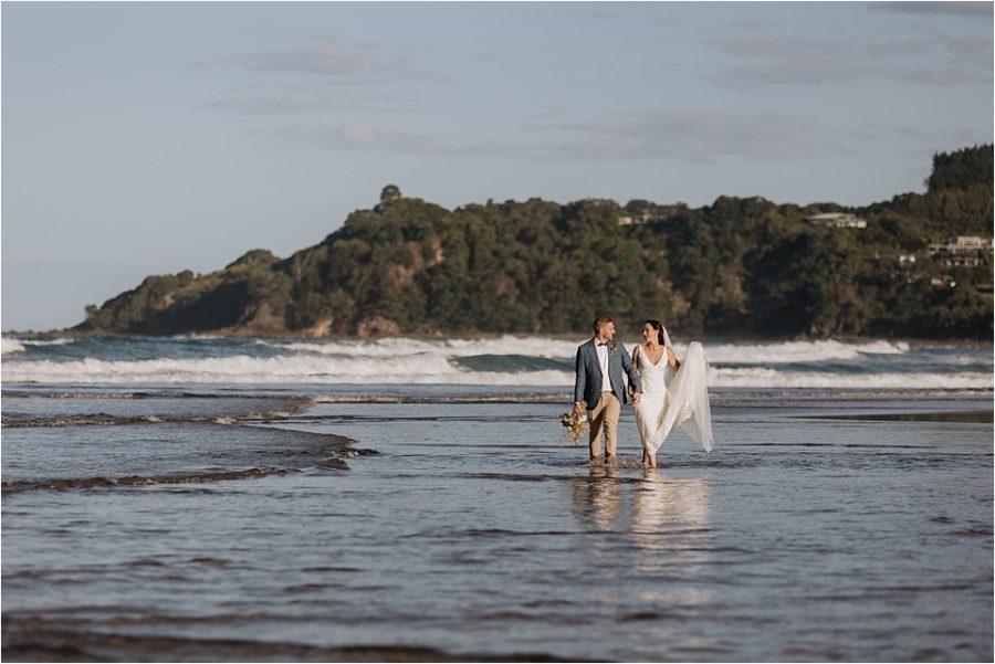 Bride and groom walking in ocean at Hot Water beach