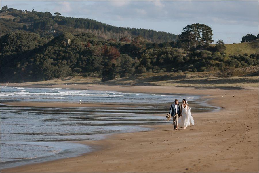 Orua Beach house Bride and Groom walking