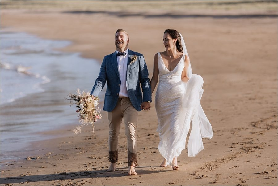 Laughing groom on Hot Water beach New Zealand
