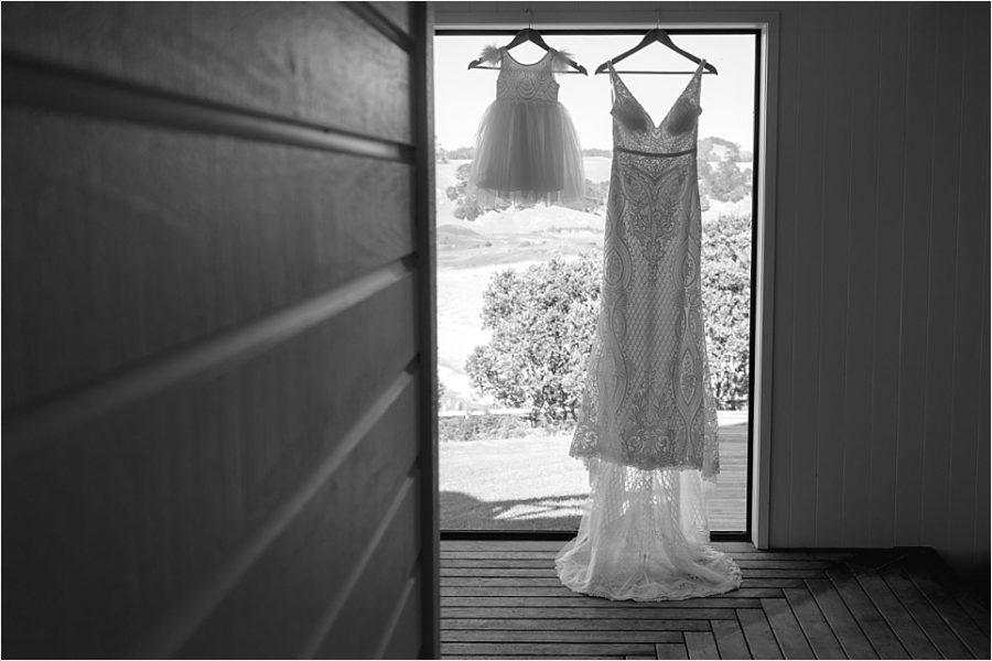 Brides dress and flower girls dress hanging at Orua Beach house