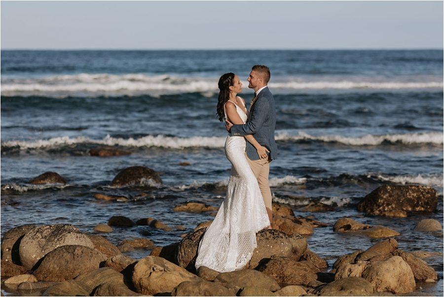 Wedding photos on rocks at Orua beach house