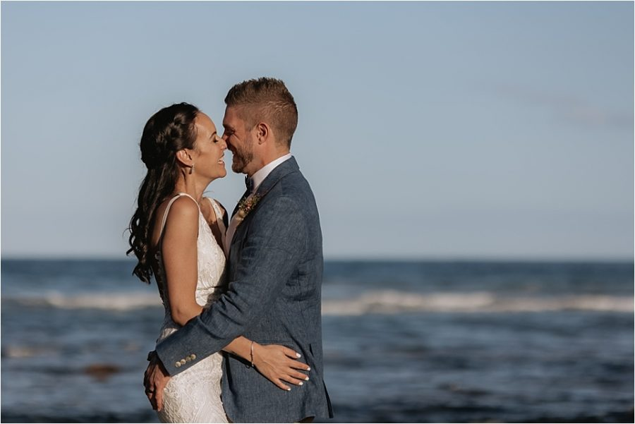 moments between Bride and groom on rocks at Hot Water beach