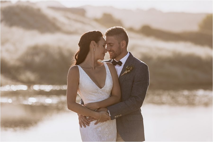 Initmate moment in golden light during wedding photography on Hot Water Beach New Zealand