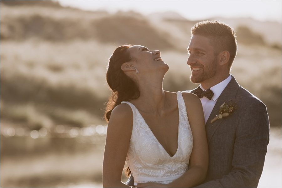 Bride laughing in golden light on Hot water beach