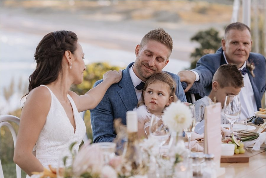 Bride and best man console groom at wedding table during speeches