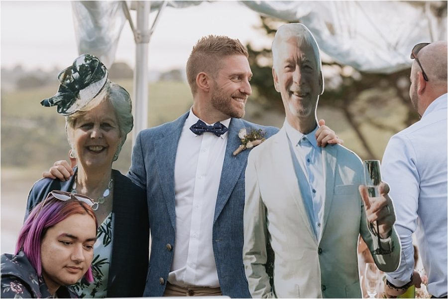 Groom with cut out of parents at his wedding