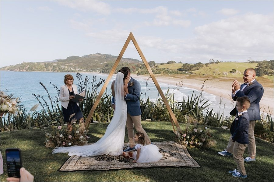 Wedding ceremony kiss over looking Hot Water beach