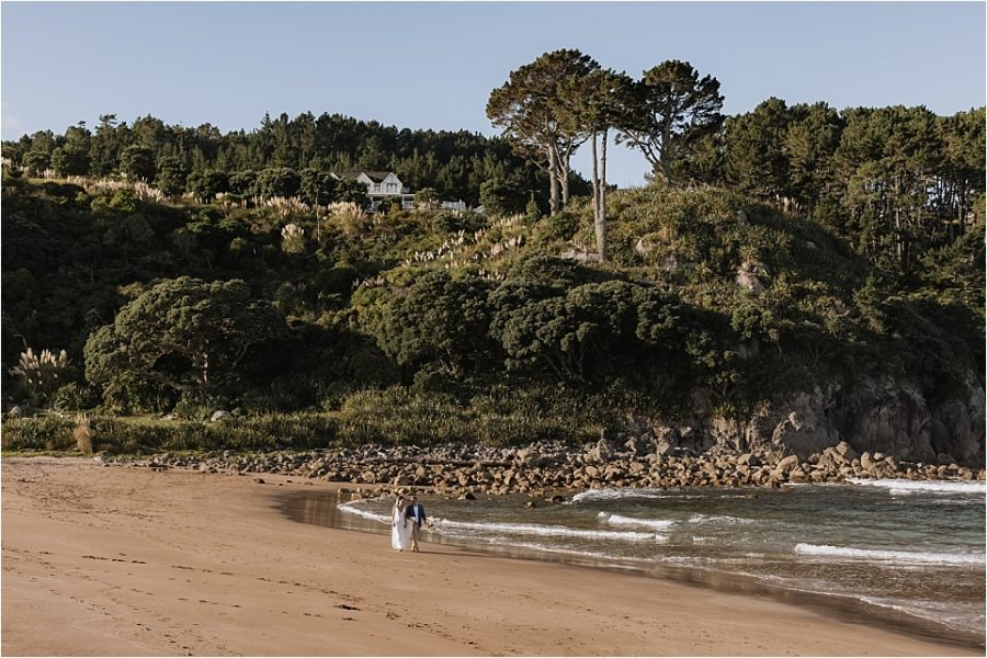 Bride and groom walking hot water beach Orua Beach house