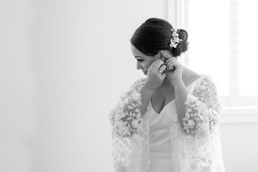 Bride getting ready as puts on earings