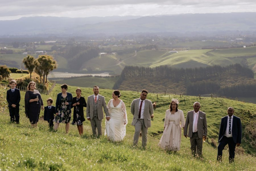 All wedding guests walking together up hill