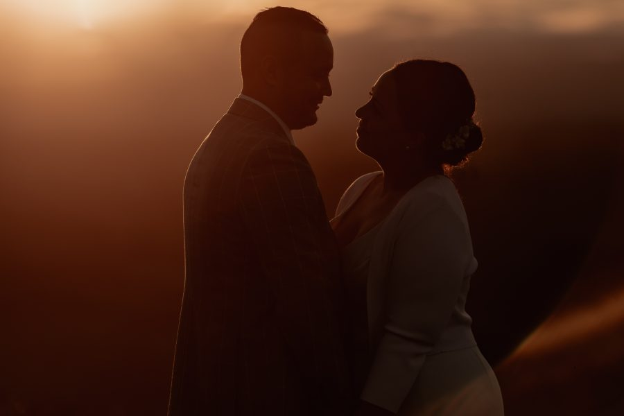 Couple looking at each other in moody wedding image at golden light