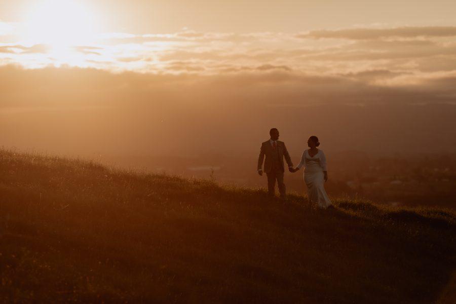 Sunset wedding photography of couple walking ridge line