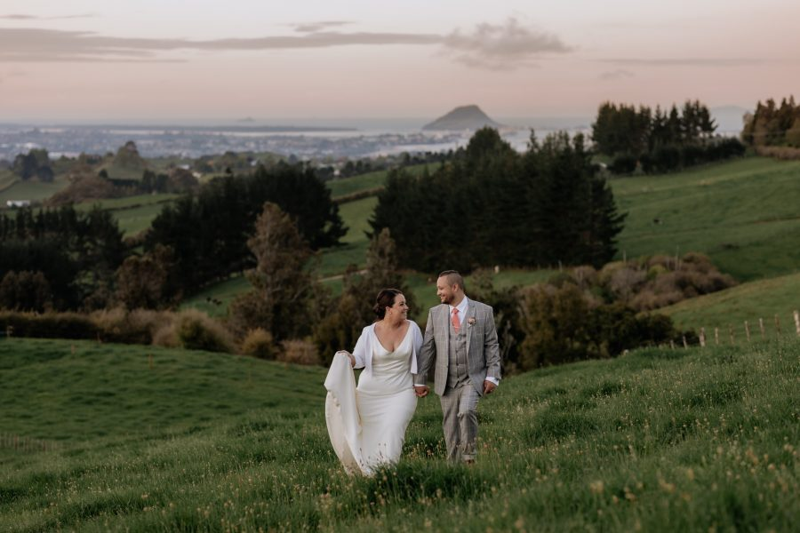 High in the hills above tauranga wedding couple walking