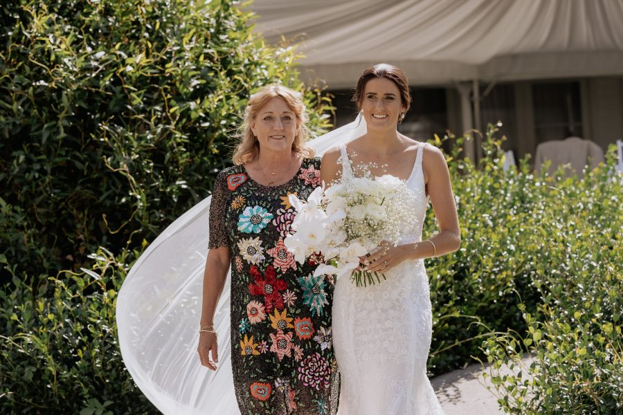 Mother walking daughter down aisle